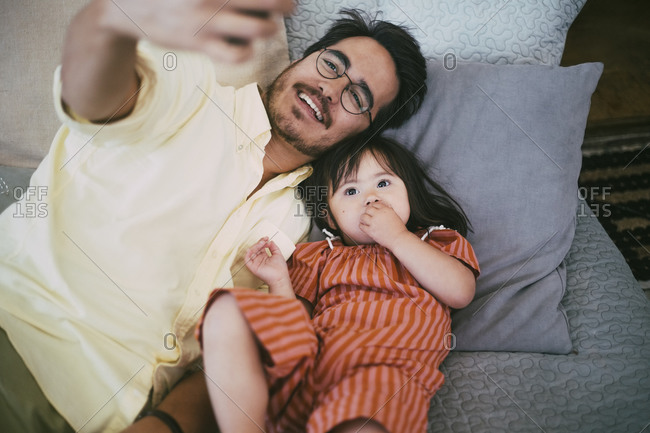 Smiling father taking selfie with down syndrome daughter while lying on sofa at home