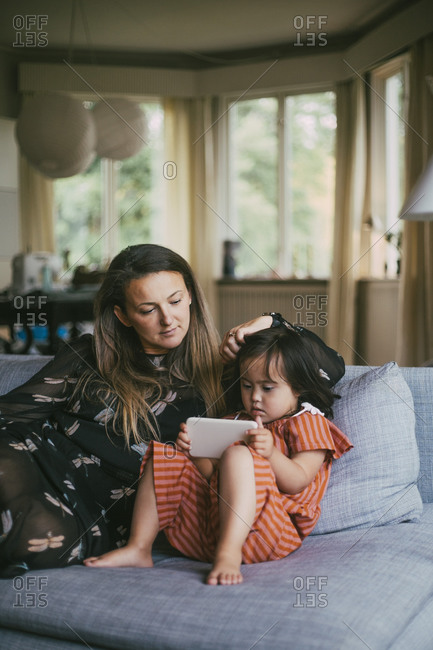 Mother looking at down syndrome daughter using mobile phone while sitting on sofa in living room