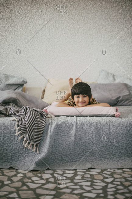 Portrait of smiling girl lying down on sofa at home