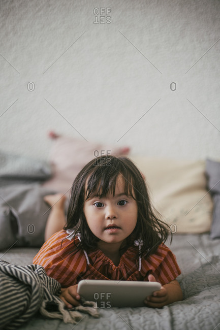 Portrait of down syndrome girl using digital tablet while lying on sofa at home