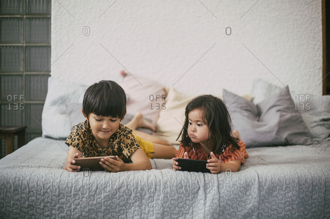 Down syndrome sister looking at sibling using smart phone while lying on sofa at home