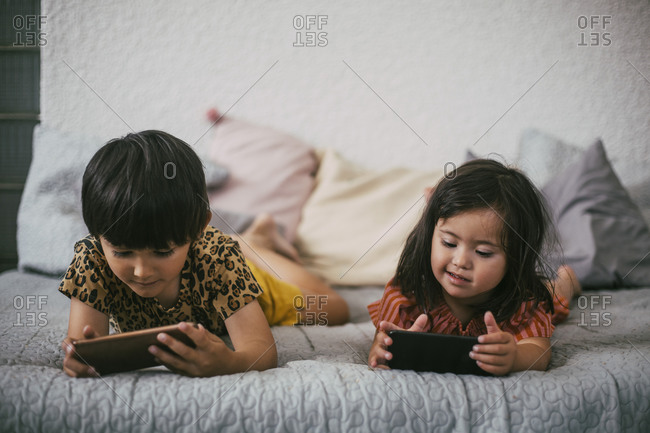 Smiling down syndrome sister and sibling using smart phones while lying on sofa at home