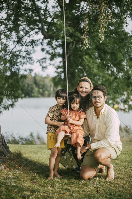 Portrait of family with down syndrome daughter enjoying summer vacations by lake