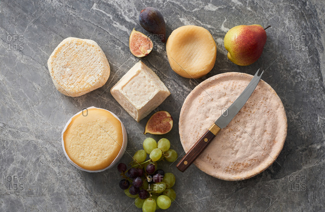 Overhead view of a cheese platter with various whole cheeses and fruit