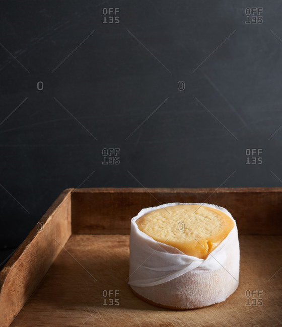 A whole artisan cheese wrapped in a muslin cloth on a wooden cheese board
