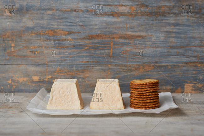 Two pyramid shaped goat cheeses with a stack of crackers