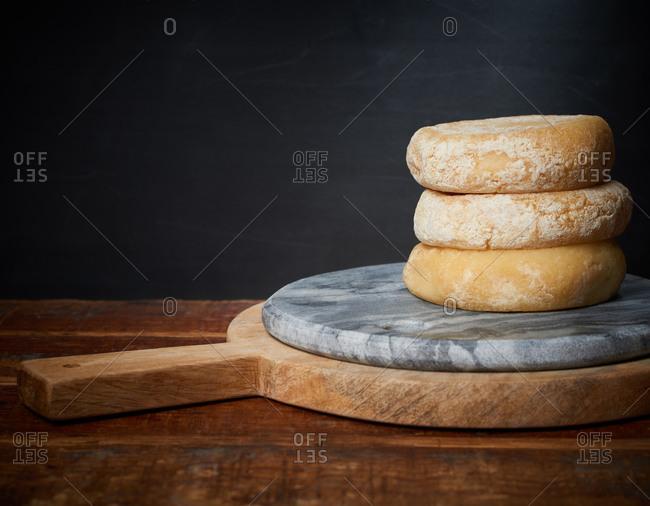 A stack of cheese wheels with aged rinds on top of marble and wooden boards