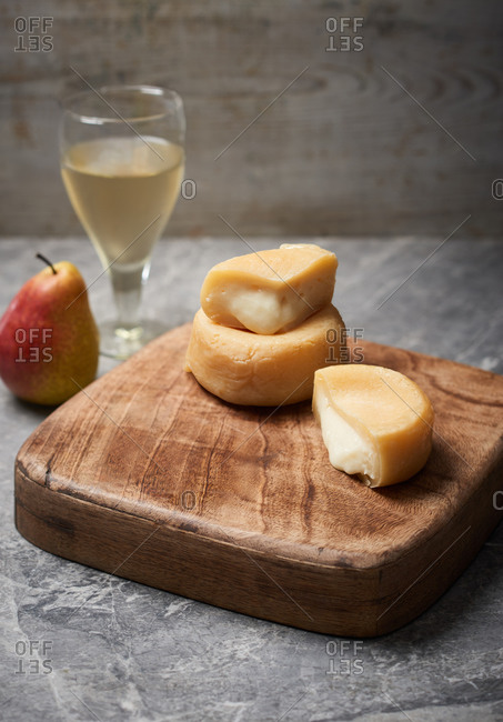 Ripe wheels of cheese served on a wooden platter with a glass of wine
