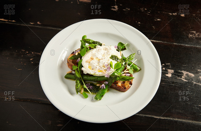 Burrata cheese served on sourdough toast with asparagus spears and chive flowers