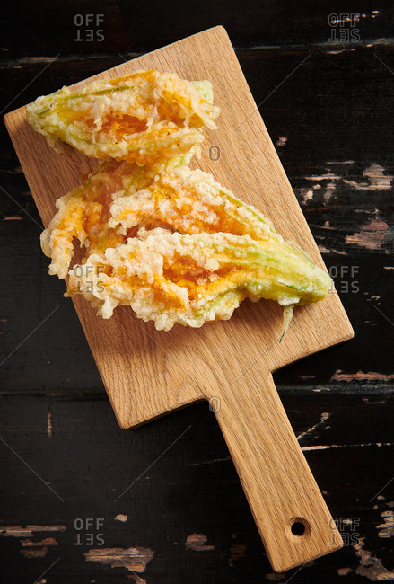 Deep fried courgette flowers stuffed with ricotta cheese served on a wooden board