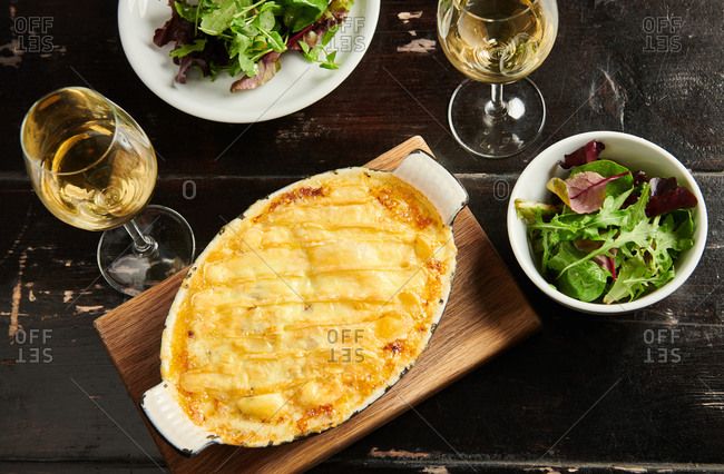 Overhead view of a French tartiflette served with white wine and salad