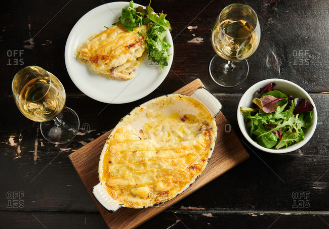 A French tartiflette gratin served with white wine and green salad