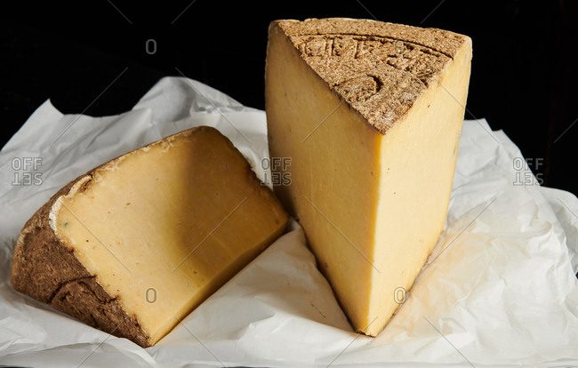 Large pieces of aged specialist cheese on white paper against a black background
