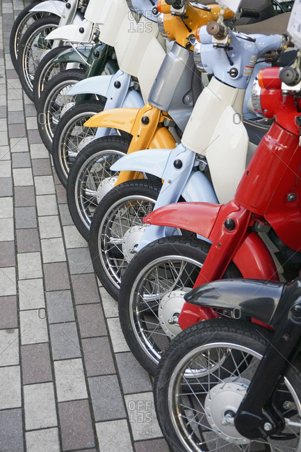 Multicolor rental motor scooters parked in a row on sidewalk, Kyoto, Japan