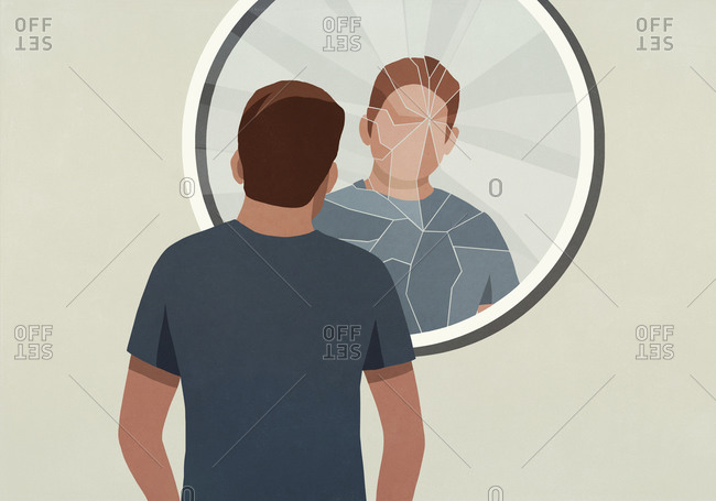 Young man looking into cracked mirror