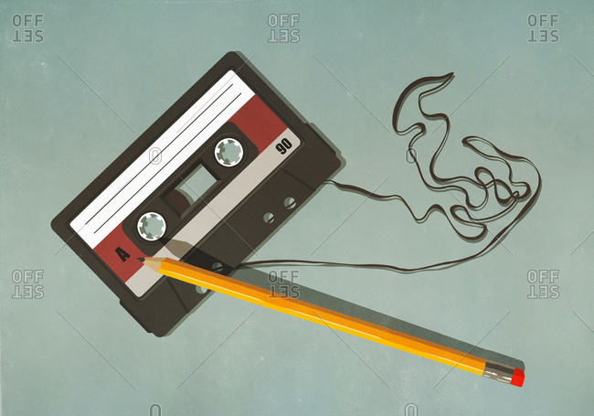 Pencil unwinding cassette tape on green background