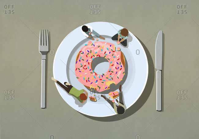 People indulging in large sprinkle donut on plate