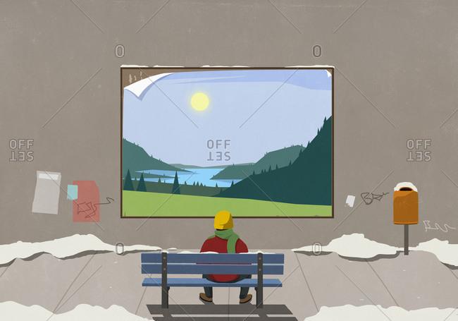 Man on urban winter bench looking at sunny rural billboard