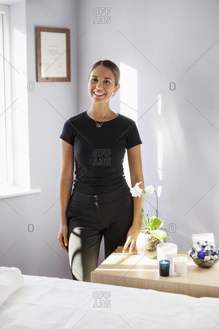 Portrait confident female massage therapist in spa room