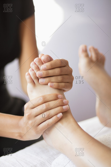 Close up female masseuse massaging client's feet