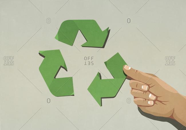 Hand assembling green recycling symbol arrows