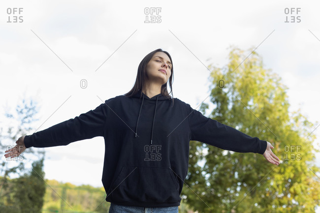 Carefree, serene young woman with arms outstretched