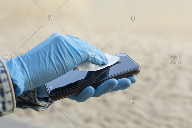 Close up woman in rubber gloves wiping smart phone screen