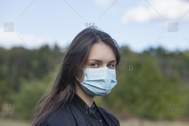 Portrait confident young brunette woman in face mask