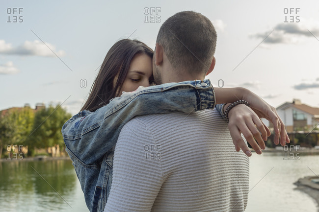 Serene, affectionate young couple hugging at lakeside