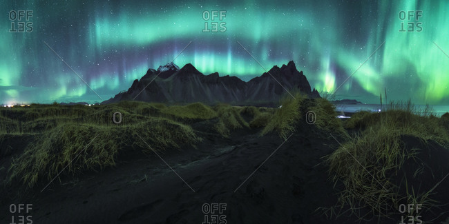 Picturesque scenery of aurora borealis over rocky terrain with mountains at dark night in iceland in long exposure