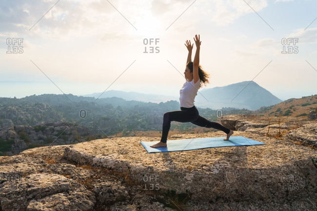 Full body of barefoot female standing in warrior pose on top of mountain while practicing yoga in nature at sunset time