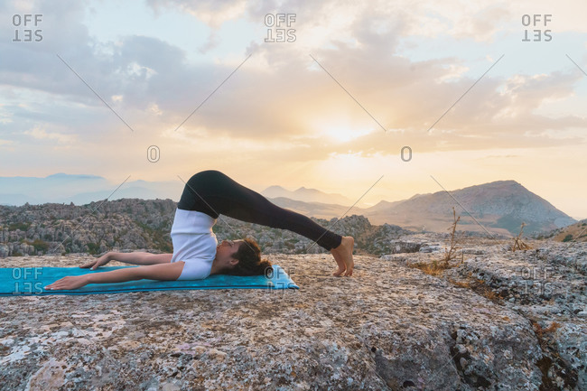 Full body side view of flexible female in activewear lying on mat and doing halasana