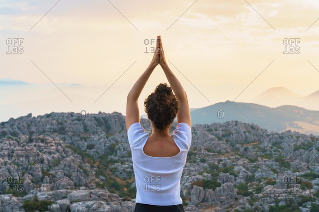 Full body back view of unrecognizable barefoot female standing in star pose