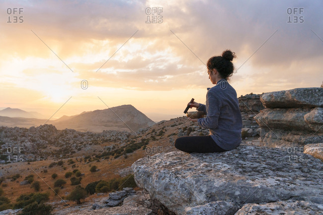 Full body side view of serene young female sitting in lotus pose with tibetan singing bowl while practicing meditation on rocky mountain at sunset