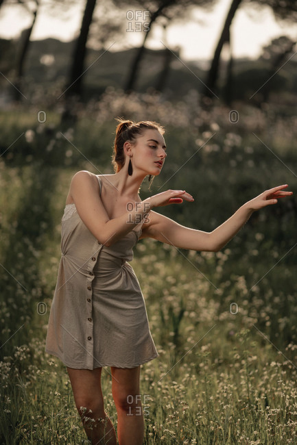 Peaceful female wearing summer dress standing on lawn in park in iceland and tenderly looking away