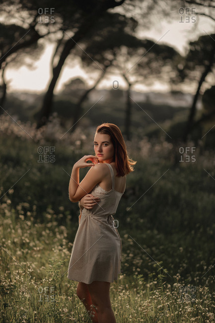 Peaceful female wearing summer dress standing on lawn in park in iceland and tenderly looking at camera