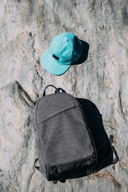 From above simple black backpack and vibrant turquoise cap on uneven surface of huge stone in sunlight