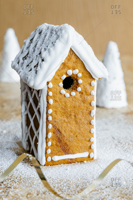 Bright delicious gingerbread house with ornament and powdered sugar with festive ribbon on table