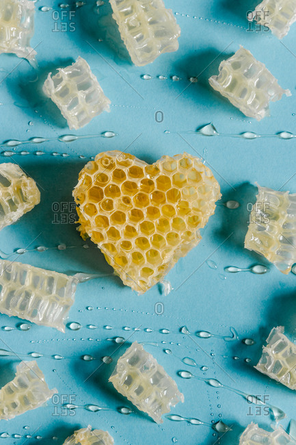 From above of bright heart shaped honeycomb with delicious honey on blue background