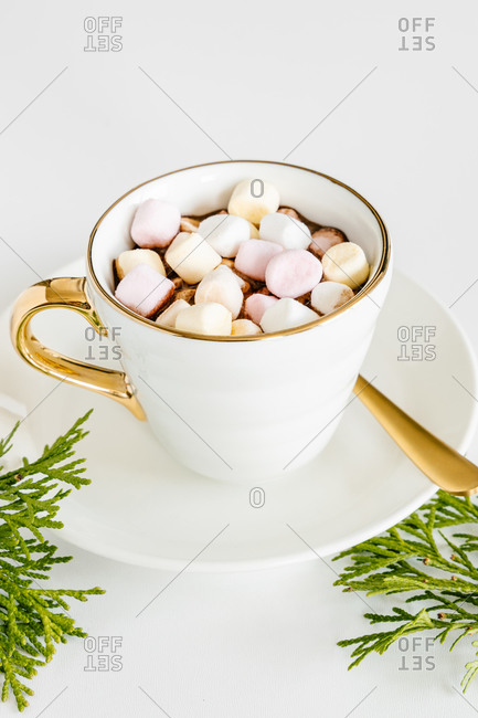From above of ceramic cup with delicious hot chocolate with sweet marshmallows on top on saucer with spoon