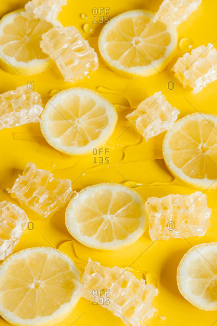 From above of honeycombs with delicious sticky honey between ripe lemon slices and drops