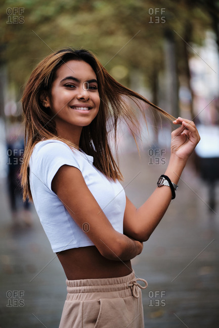 Side view of young content slim ethnic female in trendy outfit and wristwatch looking at camera in town