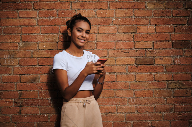 Young cheerful ethnic woman in trendy apparel standing with cellphone near rough wall on street and looking at camera
