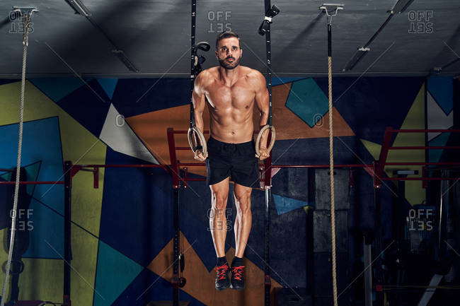 Determined strong young sportsman with naked torso doing pull ups on gymnastic rings during intense workout in gym