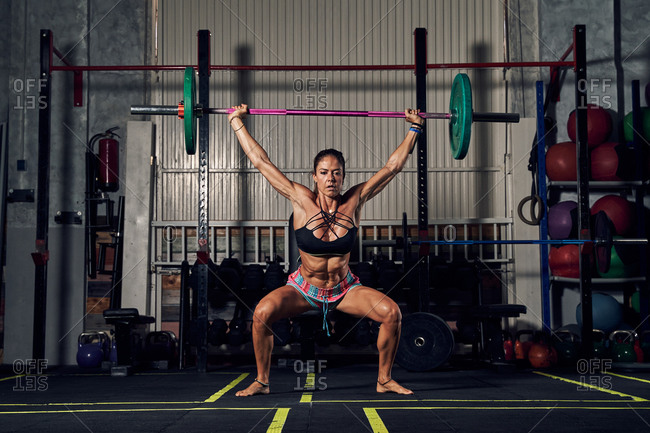 Full body of powerful young female bodybuilder in sportswear lifting heavy barbell during hard workout in gym