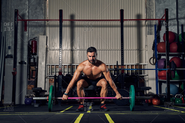 Full body of powerful young man bodybuilder in sportswear lifting heavy barbell during hard workout in gym