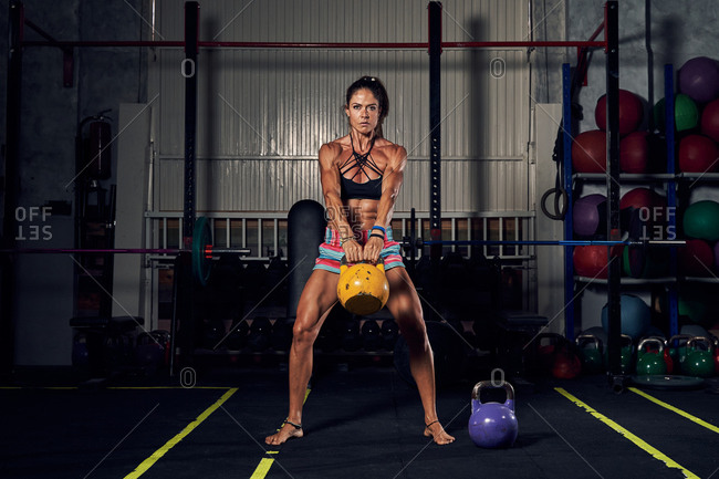 Full body of determined young female bodybuilder in activewear doing squat exercise with kettlebell during workout in gym