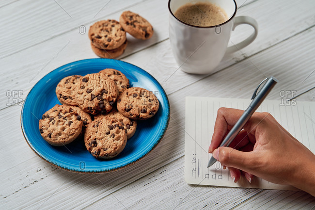 Crop  unrecognizable woman writing to do list on paper while having breakfast with mug of aromatic coffee and crispy cookies
