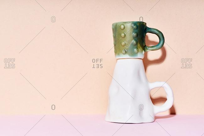 Still life of handmade ceramic mugs on bright studio background