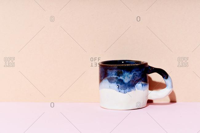 Still life of handmade ceramic mug on bright studio background